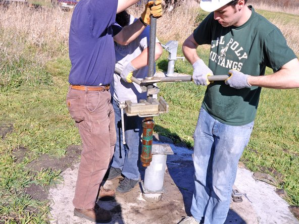 Stabilize the pipe by holding it and unbolt the base clamp from the pump base.