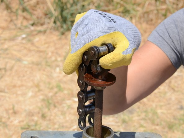 Unscrew the chain from the top of the pump rod.
