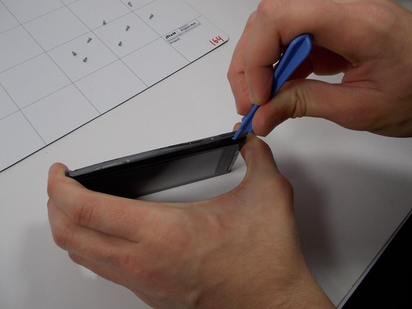 Using a case opener, start on the bottom right side of the phone and undo clips located at the interior sides. Repeat this step for the left side.