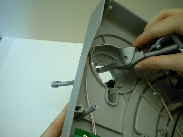 Image 3/3: Flip the turntable over and pull the tone arm all the way through the hole.