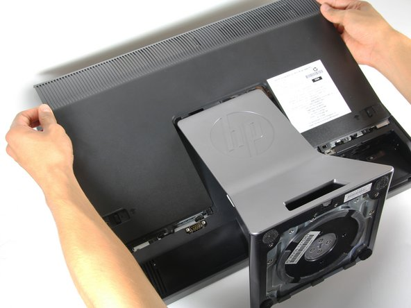 Push the unlock tabs on the back of the monitor in and towards each other while sliding the back cover up.