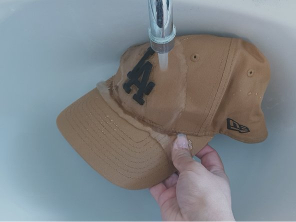 Wash the cap using an old toothbrush to remove residue and stains.
