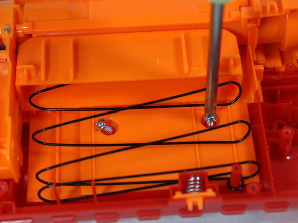 Locate the screws behind the dart pusher mechanism. Carefully remove each screw.