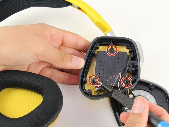 Using the Phillips #0 screwdriver, remove the three 6.4 mm screws on the black plastic panel with the grid of holes.