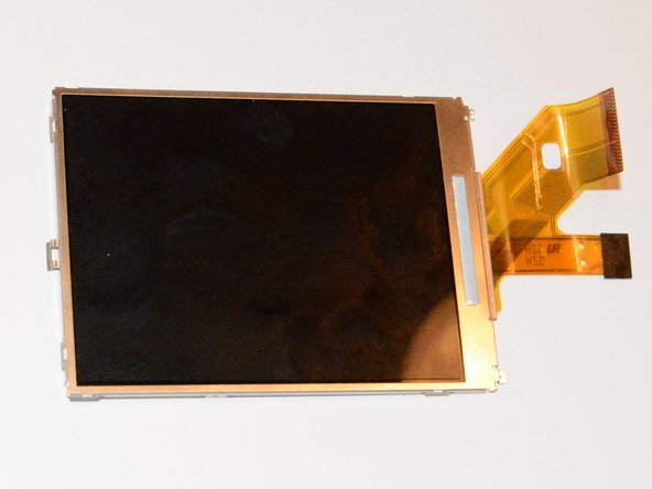 Lift the LCD from the left hand side, disengaging it at the right hand side from two small tabs.