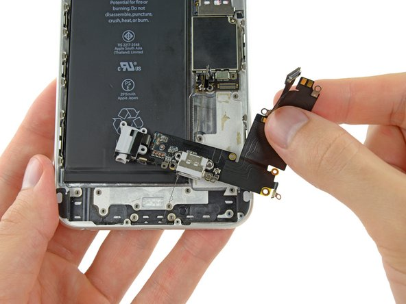 Lift and remove the Lightning connector and headphone jack cable out of the iPhone.