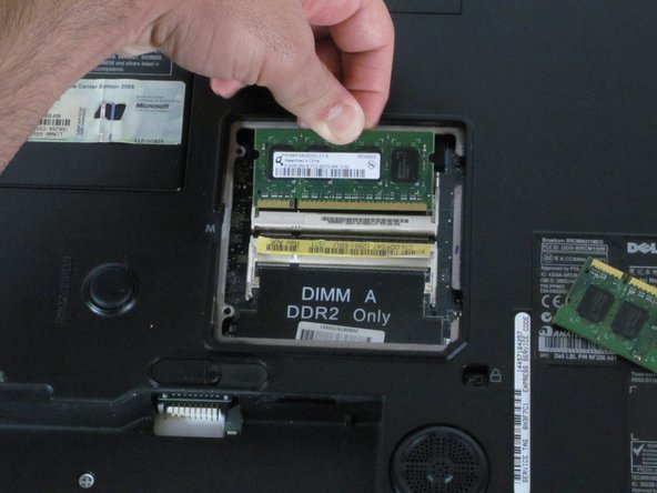 Using your fingers, pull the sides apart that are holding the RAM in place.  This will release the RAM.