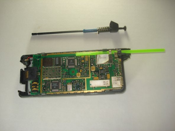 Slide the antenna out of the green tubing and slide the green tubing out of it's corresponding hole on the motherboard.