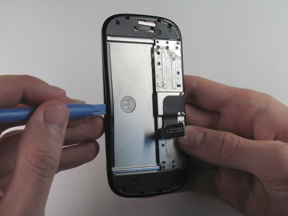 Image 1/3: Run the plastic opening tool along the edges to separate the black plastic cover from the display assembly.