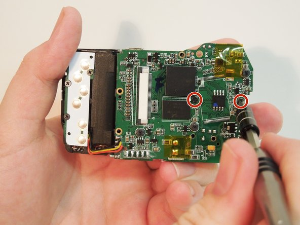 Remove the two screws holding the lens assembly to the motherboard using the PH00 bit screwdriver