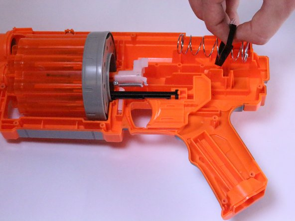 Using your hand, lift the large spring and attached plastic stabilizing piece out of the gun and set aside.
