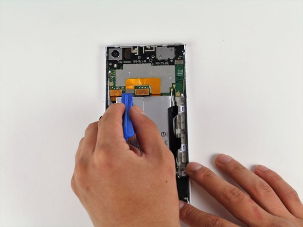 Use the iFixit Opening Tool to remove the flexible orange strip which connects the battery to the motherboard.