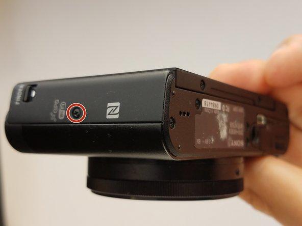 Entferne die markierte Schraube an der Seite der Kamera mit einem Kreuzschlitzschraubendreher #000.