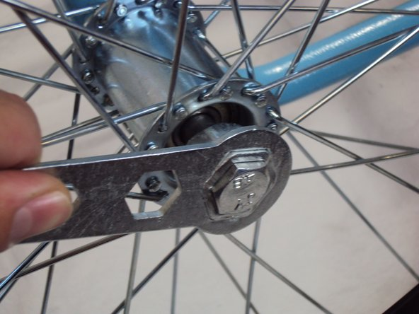 Image 1/2: '''Unscrew''' the bolt on the outside of the wheel by using a 19 mm socket wrench.