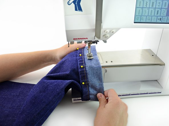 Insert the pant leg into the sewing machine, sliding the cuff around the arm of the sewing machine.