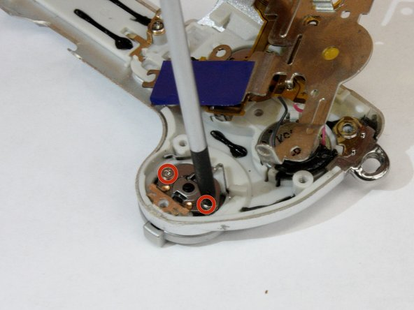 Lift up the metal frame to expose the two screws located under the trigger button.