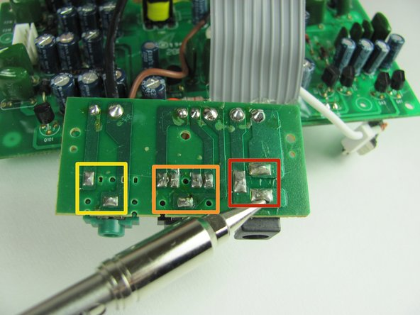 Turn the circuit board over so the solder is visible. Depending on which input is broken remove the solder connecting either the Auxillary, DC, or Sub input.
