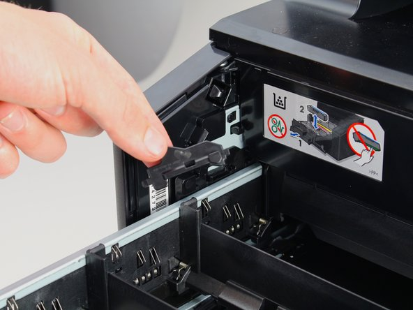 Pivot the back end of the lock away from the inner wall of the printer and towards you until it pops out.