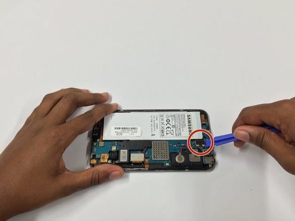 Using the plastic opening tool, apply an upward force to detach the battery and the tab attached to it.