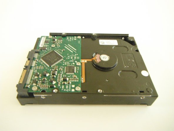 Unscrew the four 5mm screws on both sides of the hard drive using the Phillips #1 screwdriver and then remove the hard drive from the case.