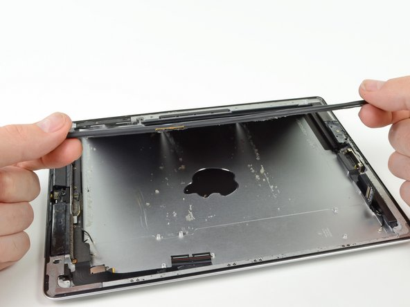 Gently lift the left side of the battery up, rotating it toward the right side of the iPad.