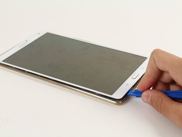 Move the plastic opening tool in a downward motion until you see separation between the tablet and back cover.