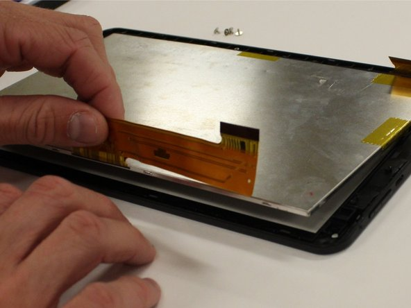 Once the screen is pried free from the digitizer, simply grab the thin orange circuit strip and carefully pull in an upwards motion to remove the screen from the digitizer. Set screen to the side.