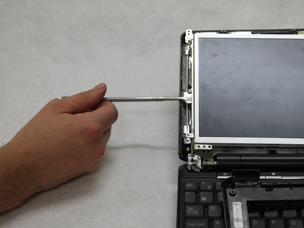 Use the metal spudger to gently remove the screen from the laptop.