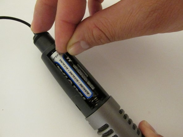 To remove the battery, push it upward into the aluminum spring. This will loosen and free the battery.