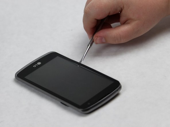 Slide the metal spudger along the perimeter of the phone in order to break the entire seal.