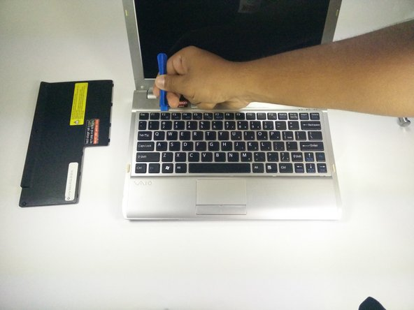 Use a plastic opening tool tool to pry around the edge of the keyboard.