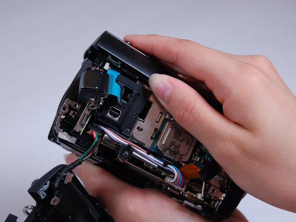 Pull off the top casing by lightly grabbing either side and pulling towards the back of the camera.