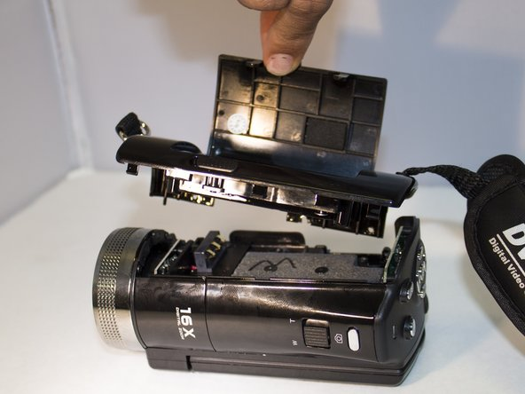 Image 1/1: Gently pull up on the side panel to remove it from the camera.