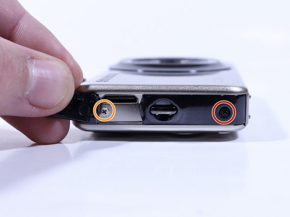 Slide memory card cover and unscrew hidden screw  underneath with a #00 Phillips driver.
