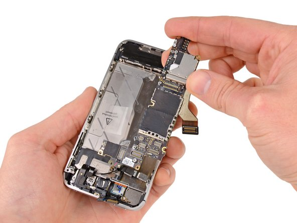 Carefully lift the logic board from the end closest to the speaker enclosure and slide it away from the top edge of the iPhone.