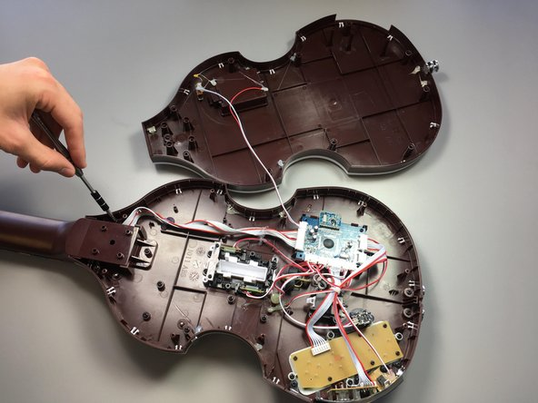 Pull off the back whole panel so that the guitar is now open.