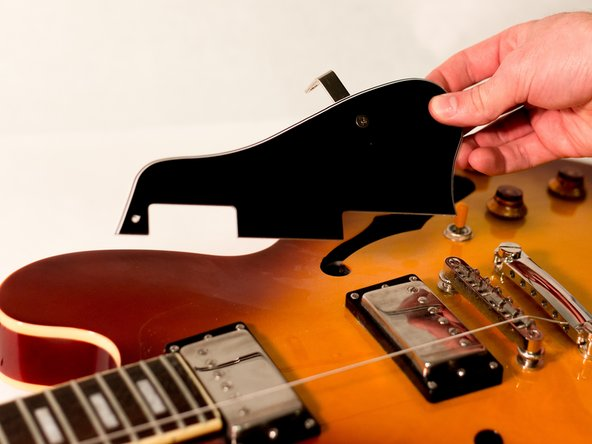 Gently lift the pickguard off the body of the guitar.