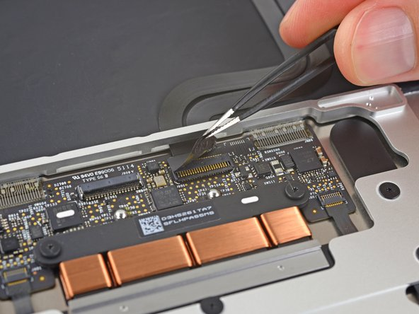 Use a pair of tweezers to remove the tape covering the keyboard ribbon cable connector on the trackpad.