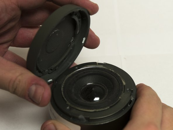 Use the plastic opening tool to separate the speaker grate from the rest of the device.