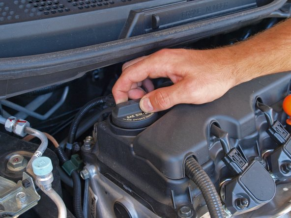 Remove the oil filler cap at the passenger side of the engine by twisting it counter-clockwise then lifting it off of the oil filler hole.