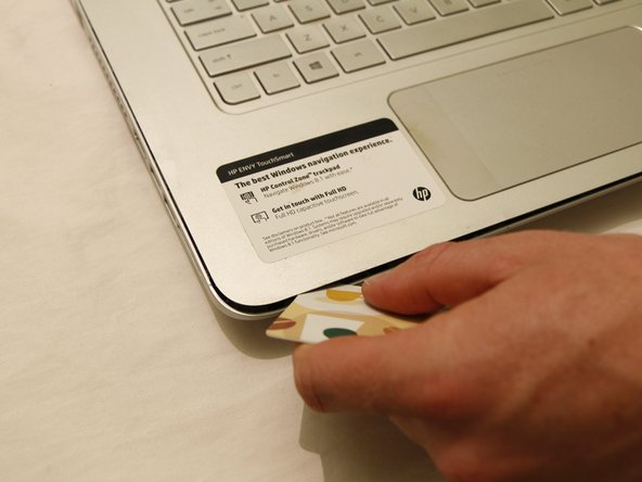 Slide the card all the way around the laptop, making sure to pop free all tabs.