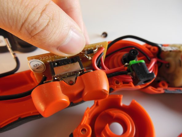 Carefully grip the circuit board on the exposed edge and lift it away from the drill as far as is possible.