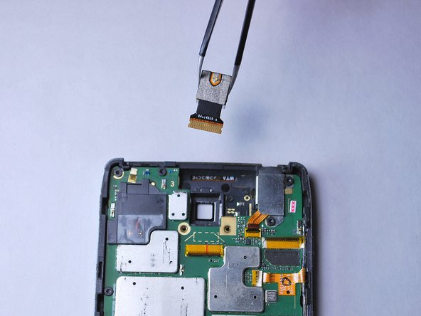 Use tweezers to gently remove the rear-facing camera by lifting it up off of the motherboard.