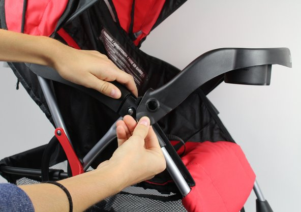 "Unsnap the ""Child Tray"" by pulling outwards on the plastic connectors on either side of the stroller.  As you pull, lift upwards to completely remove the tray from its connection to the stroller's frame."
