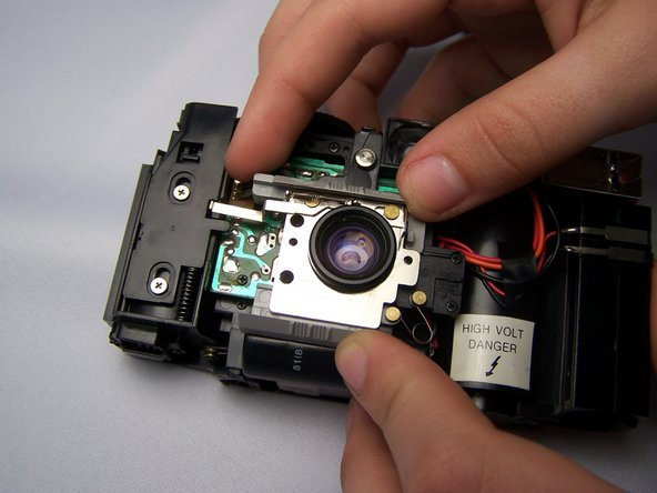 Pull aside the top plastic piece resting on the metal lens plate in order to access the other screws.