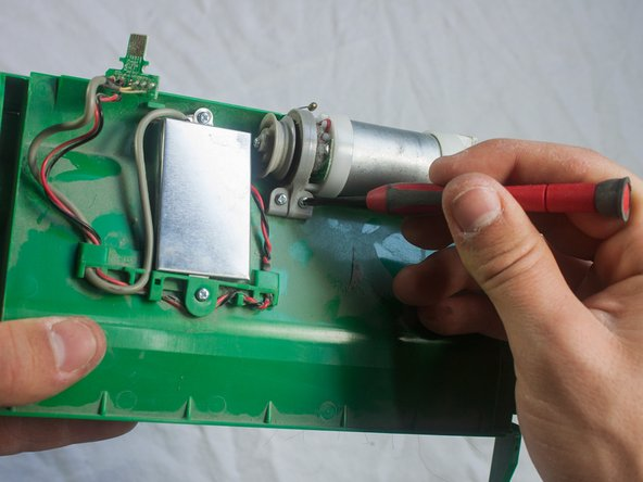 Use a Phillips #1 screwdriver to remove the two 5.5mm screws securing the motor in place.