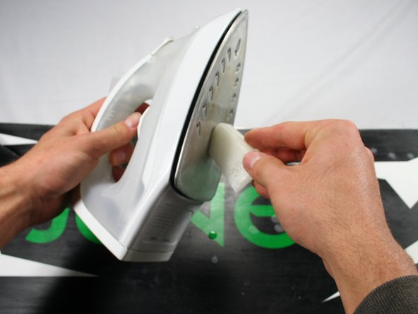 Image 1/2: Let the wax drip off the iron and onto the snowboard. Cover the entire board evenly with drips.