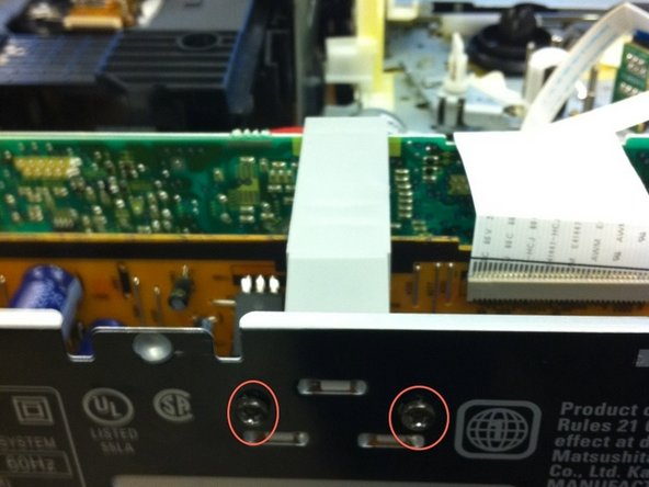 Remove two screws shown in the second image.  Remove the gray connector on top of the input board.