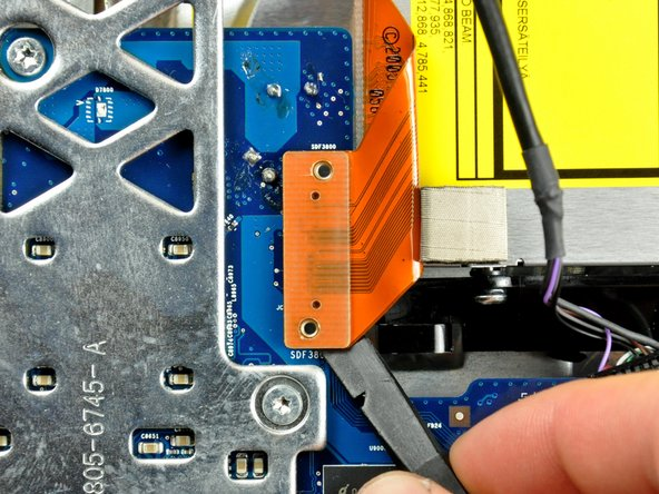 Image 1/1: Use the flat end of a spudger to pry the optical drive ribbon cable connector up off the logic board.