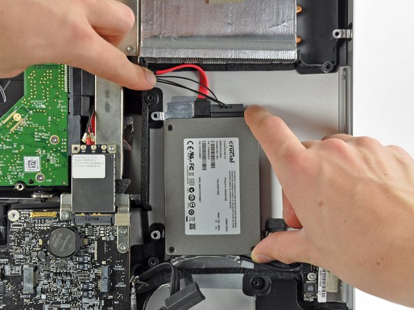 Carefully set the drive into the iMac optical bay as close to the lower left corner as possible.